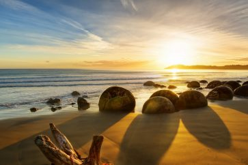 new_zealand_ocean_sunrise_rocks_coastline_79361_2560x1080