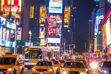 Traffic jam in the Times Square New York City streets with yellow cabs at night.